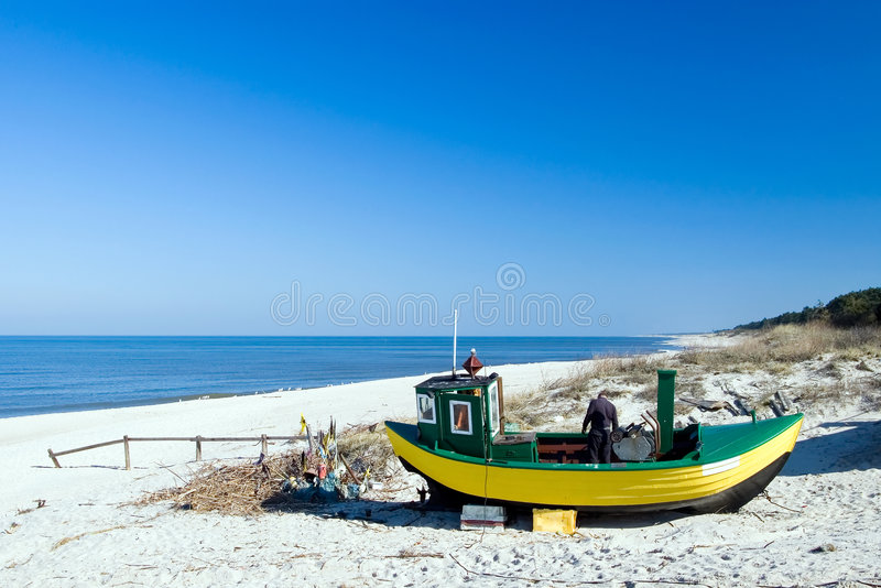Yellow fishing boat. A yellow fishing boat standing on the sand of a beach, a fisherman in the boat, empty beach. The Baltic Sea stock photo