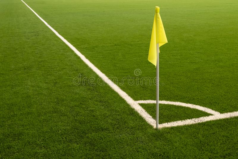Place for a corner kick. Yellow flag, white marking line on a green sports field. Football field without people. Yellow flag, white marking line on a green royalty free stock image