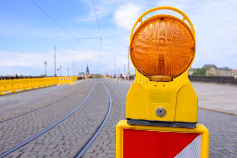 Yellow flashing light standing at road construction site. Road works concept. Yellow flashing light standing at road construction site. Road works concept stock image