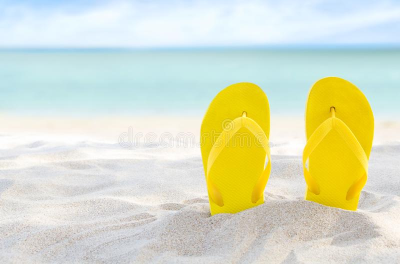 Yellow flip flops on beach sand texture and tropical sea background. Summer holidays and hot season. Fun ocean weekend. Summertime. Selective focus royalty free stock images