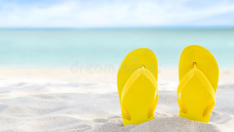 Yellow flip flops on beach sand texture and tropical sea background. Summer holidays and hot season. Fun ocean weekend. Summertime. Selective focus. Banner royalty free stock image