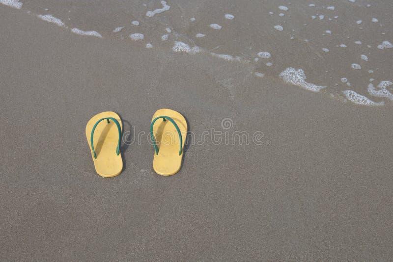 Yellow flip-flops footware pair on the beach sand.  stock photo