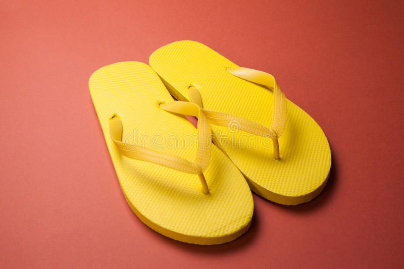 Yellow flip-flops. On a red wooden background stock image