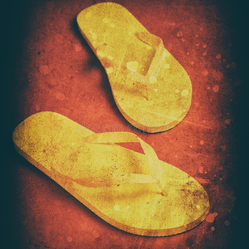 Yellow flip-flops. On a red wooden background stock photography