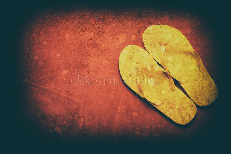 Yellow flip-flops. On a red wooden background stock photo