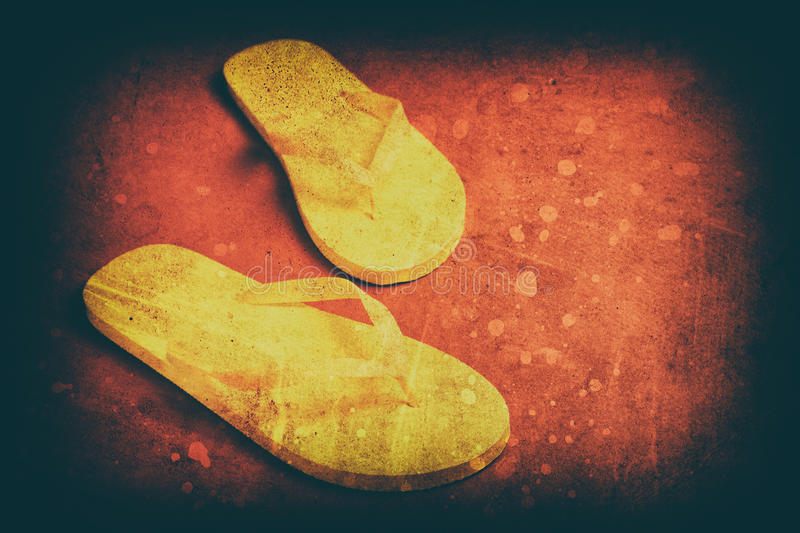 Yellow flip-flops. On a red wooden background royalty free stock images