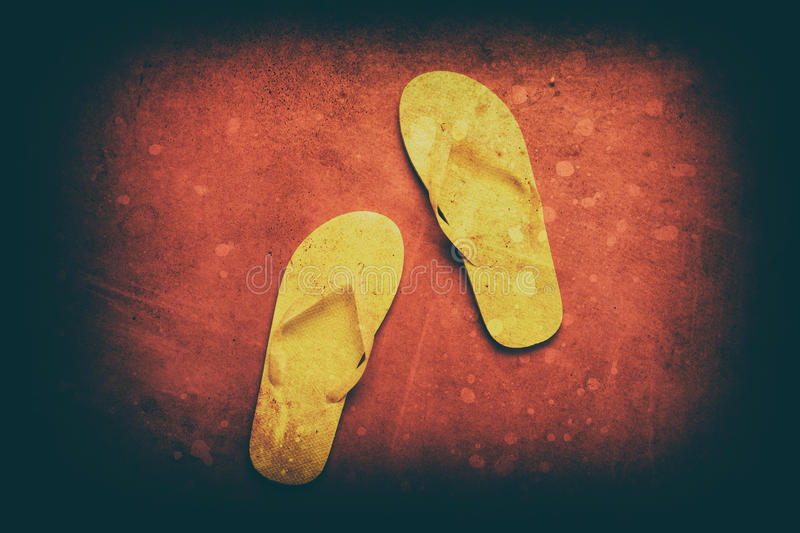Yellow flip-flops. On a red wooden background royalty free stock photo