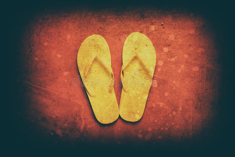 Yellow flip-flops. On a red wooden background stock photos