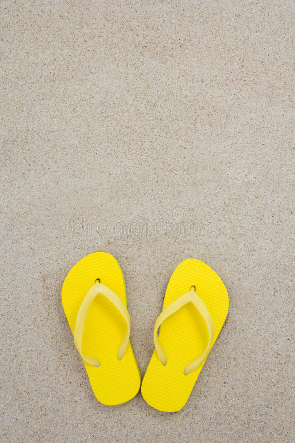Yellow flip flops on the white beach sand. With copyspace stock image