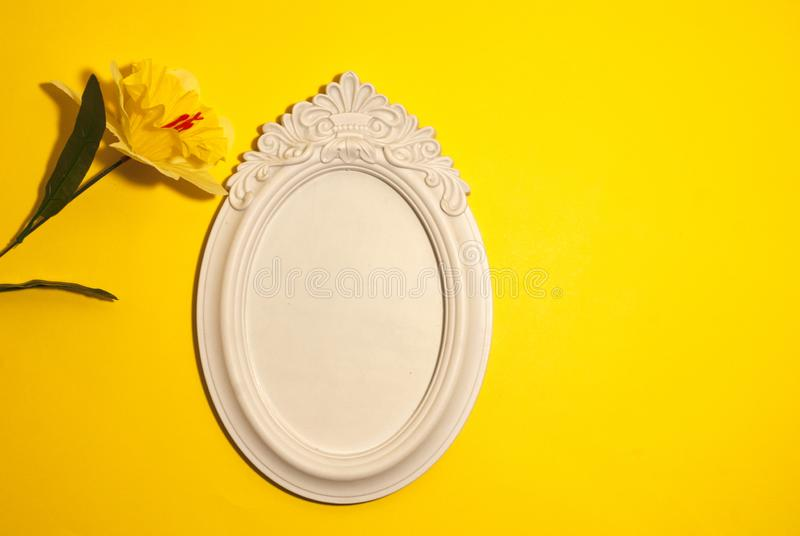 Yellow flower on a yellow background with  an empty place for a photograph. Yellow flower on a yellow background with an empty place for a photograph stock image