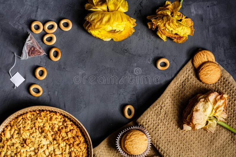 Yellow flower, cookies and apple pie lying on gray background. Flat lay. Top view stock image