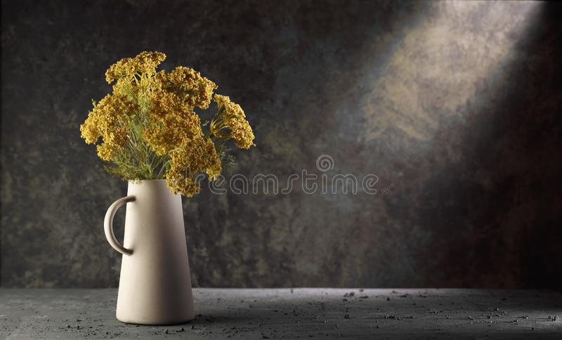 Yellow flowers in a vase on dark background with dramatic light. Yellow flowers on a vintage background, dramatic light brown vase stillife photography royalty free stock photography