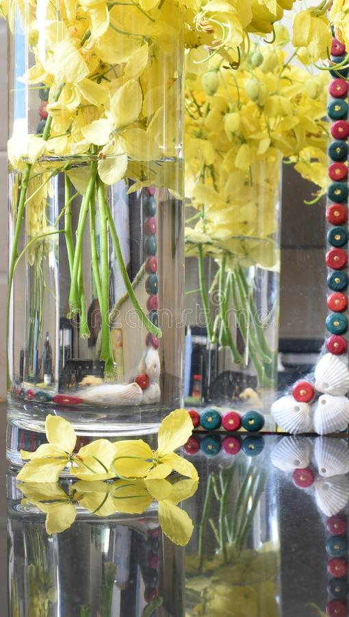 Yellow flowers in water vase with its reflection on floor and on mirror in the backdrop royalty free stock image