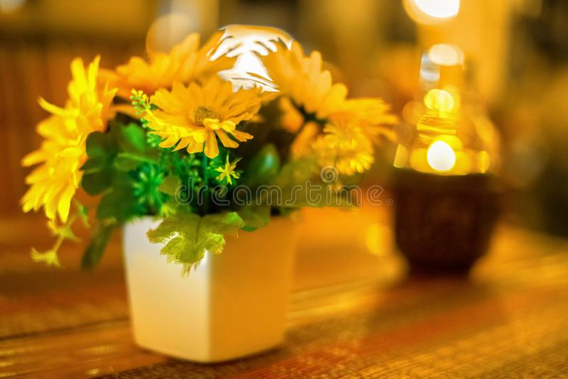 Yellow flowers in a white pot on a wooden table. next to the lamp with a candle in the form of a bottle. table stock photography