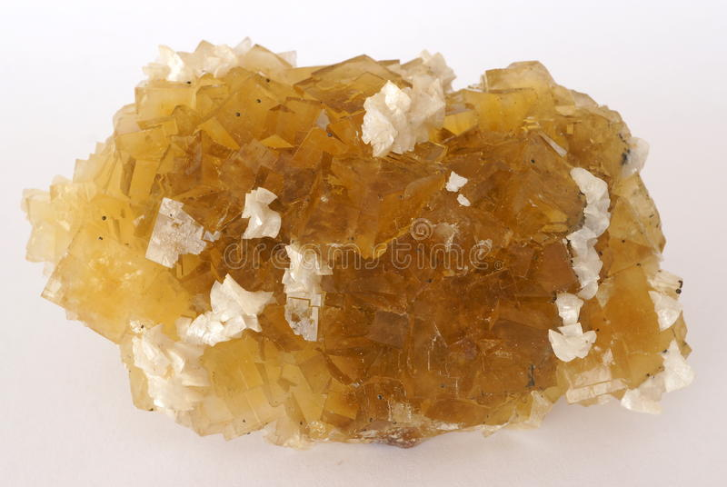 Yellow Fluorite crystal cluster. A cluster of yellow cubic Fluorite crystals with some small pieces of white Dolomite stock photos