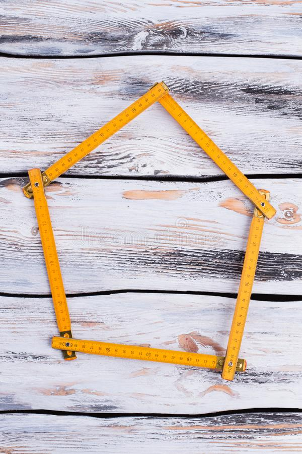 Yellow folding ruler forming shape of house. House-shaped yellow wooden folding ruler. House design concept royalty free stock photo