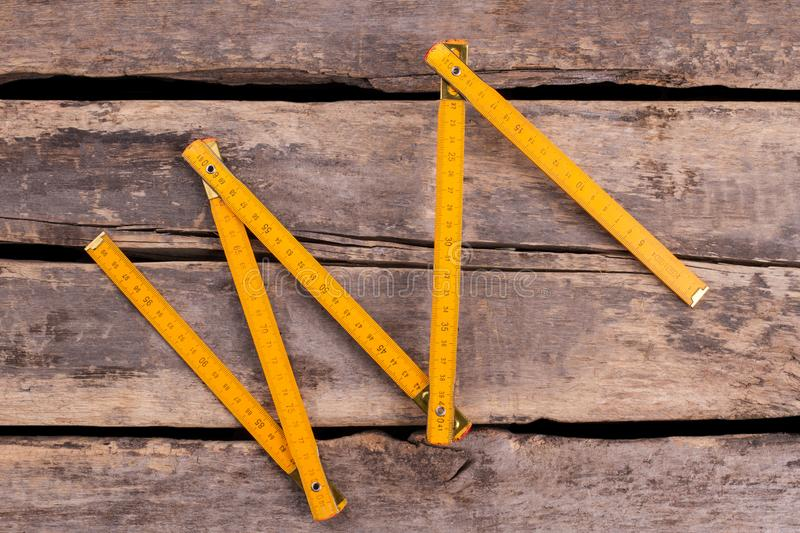 Yellow folding ruler on wooden boards background. Measuring tool on cracked rustic planks stock photography