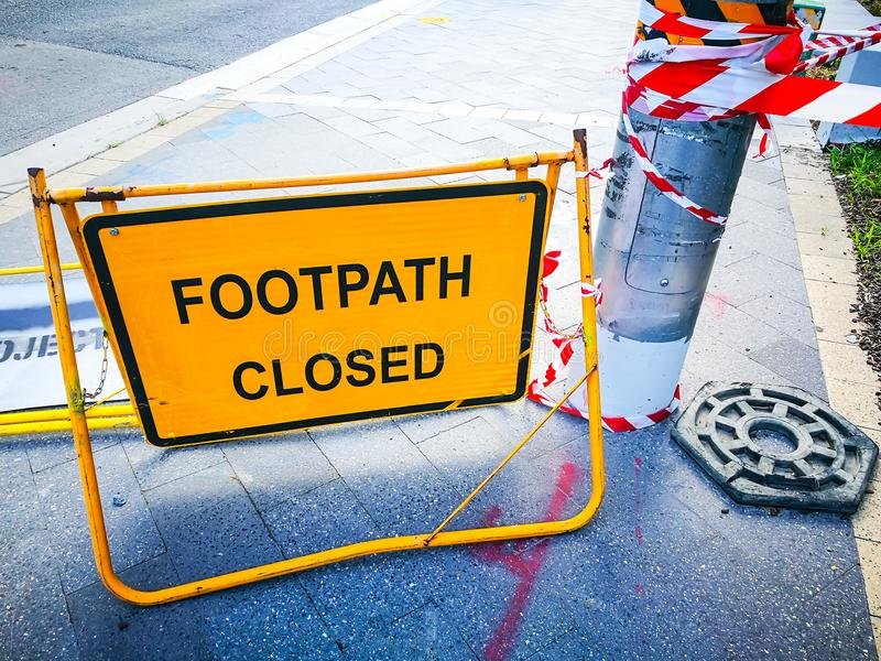 Yellow footpath closed signs putting on pavement. Yellow footpath closed caution signs indicates a potential hazard, obstacle or condition requiring special stock photography