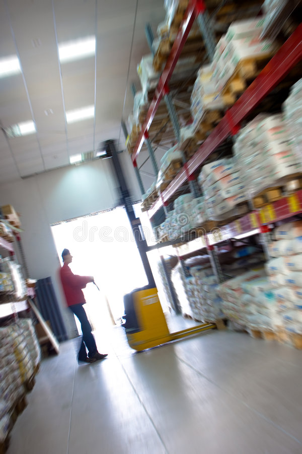 Yellow fork lifter work in big warehouse. In blur. royalty free stock photo