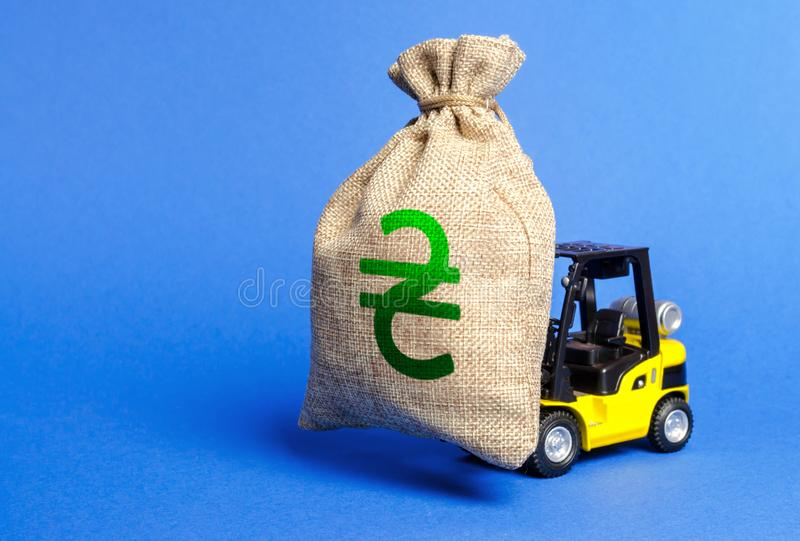 Yellow forklift carries a money bag with Ukrainian hryvnia symbol. Concept of a major contract, profitable deposit or loan. Payment of taxes. escape of royalty free stock images