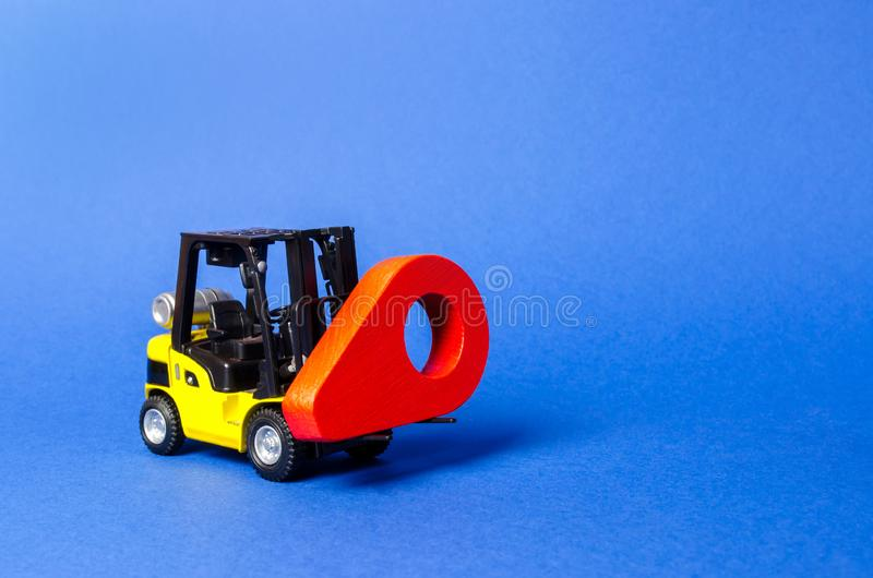Yellow forklift carries a red location pointer. Destination cargo and parcels, tracking. Technological processes at factory royalty free stock photo