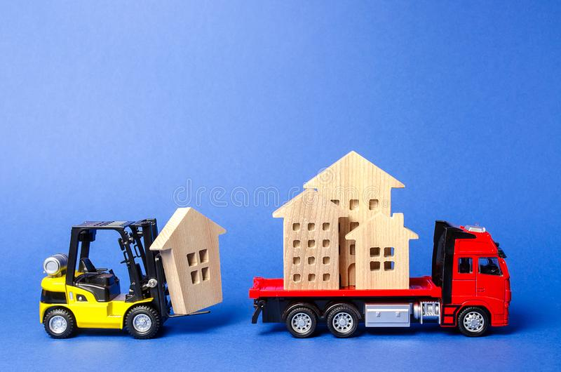 A yellow forklift loads a house figures on a red truck. Concept of transportation and cargo shipping, moving company. Construction. Of new houses and objects stock photos