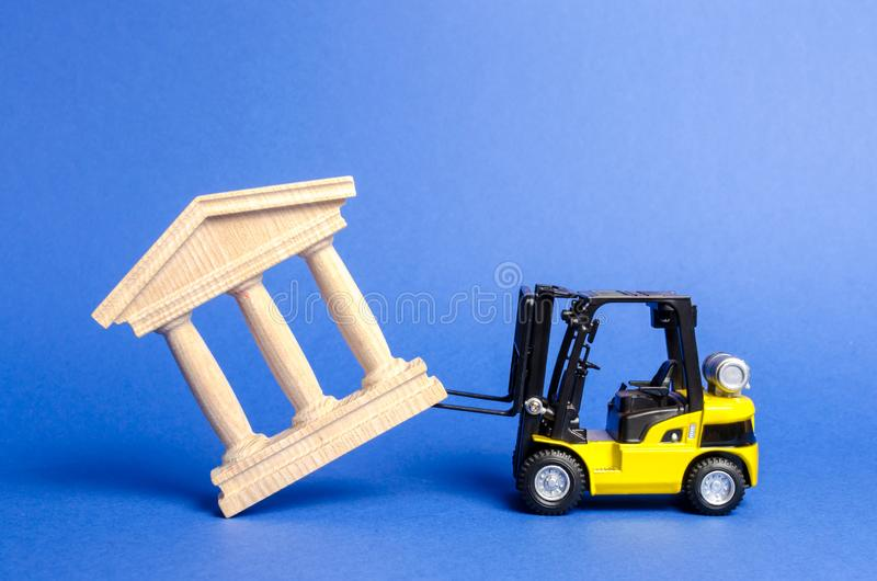 Yellow forklift overturns a government building. Bank, museum, monument of architecture. Dismantling power, protests stock photos