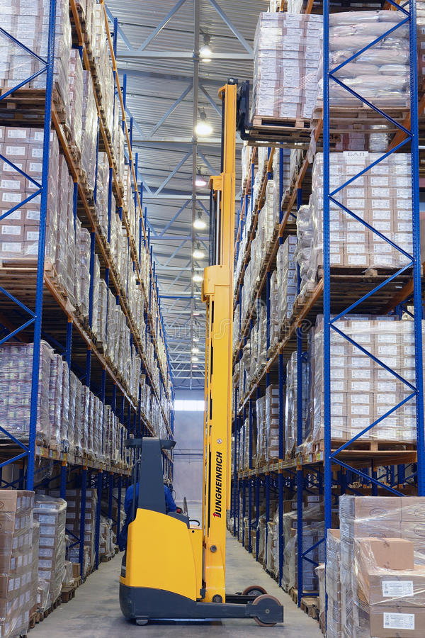 Yellow forklift raises palletising on top shelf of the rack. royalty free stock image