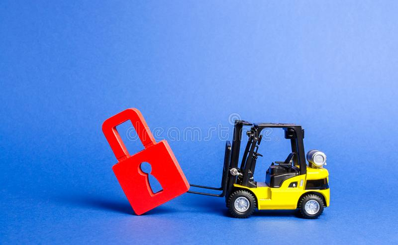 A yellow forklift tilts a red padlock from the road. Bypassing prohibitions and sanctions restrictions, lobbying the interests stock image