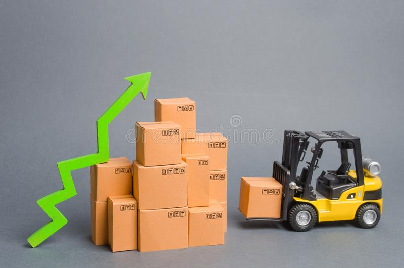Yellow Forklift truck brings the box to a stack of boxes and a green arrow up. raise economic indicators. exports, imports. sales. Rise. High trade volumes stock photography
