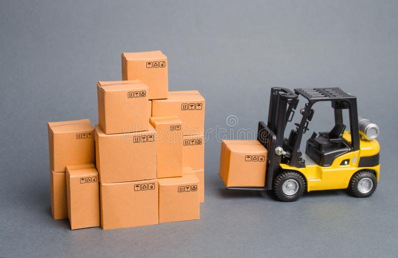 Yellow Forklift truck brings the box to a stack of boxes. Industry and Production. warehouses and transportation. raise economic. Indicators. exports, imports royalty free stock photos