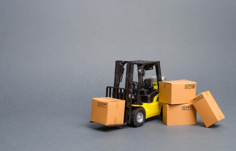 Yellow Forklift truck with cardboard boxes. Increase sales, production of goods. transportation, storage of cargo and goods stock photo