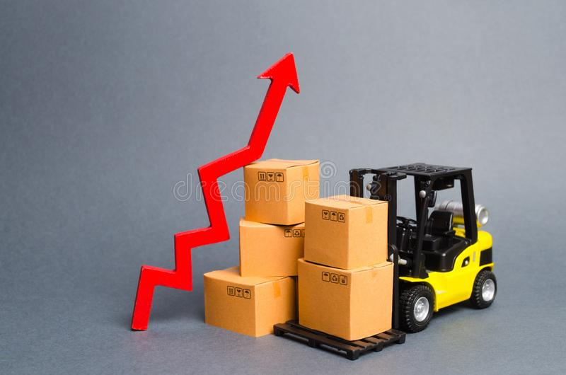 Yellow Forklift truck with cardboard boxes and a red arrow up. Increasing consumer demand. growth rate of production goods. And products, raise economic stock photo