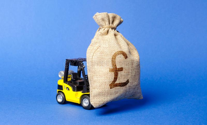 Yellow forklift truck carries a bag of pound sterling. Attracting investment in development, modernization of production royalty free stock photos