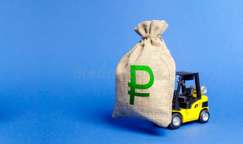 Yellow forklift truck carries bag of russian ruble money. Attracting investment in development, modernization of production royalty free stock images