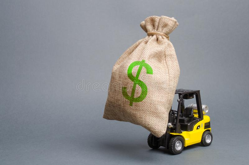 Yellow forklift truck carries a big bag of money. Attracting investment in the development and modernization of production royalty free stock photography