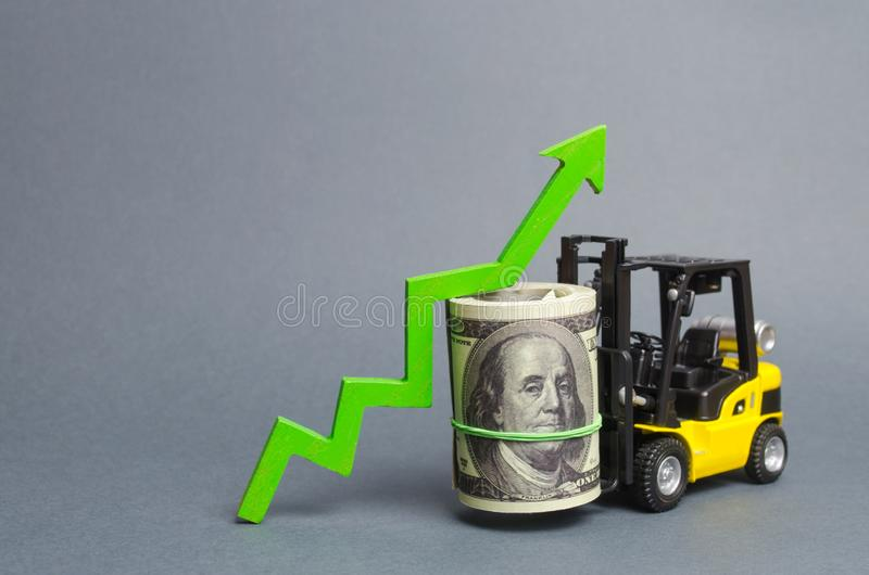 Yellow Forklift truck carries a big bundle of dollars and green up arrow. Growth of income and profit. progress of industrial. And logistics industries, wage stock photo