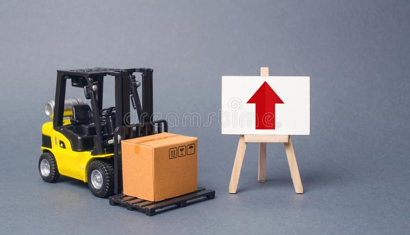 Yellow Forklift truck carries a box next to an easel with a red up arrow. Increasing the pace of production of goods and services royalty free stock images