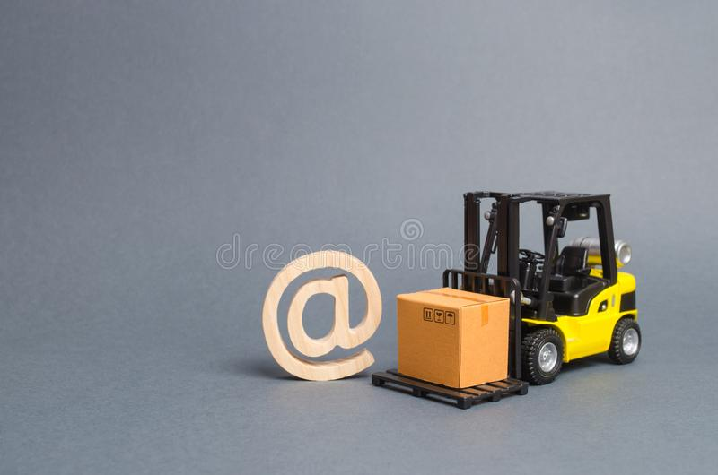 Yellow Forklift truck carries a cardboard box near a email symbol commercial AT. development of Internet network trade. E-commerce. Sales of goods through stock image