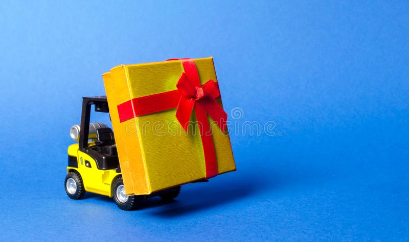Yellow forklift truck carries a golden yellow gift box with a red bow. Purchase and delivery of a present. retail, discounts. Yellow forklift truck carries a royalty free stock photo