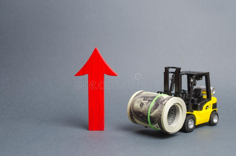 Yellow Forklift truck carries a large bundle of dollars and a big red arrow up. Growth of revenue and profit. development royalty free stock photo
