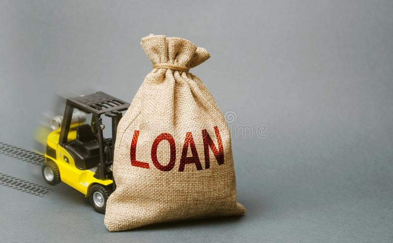 Yellow forklift truck crashed into the bag with the word loan and can not lift it. Inability to repay a loan, debt restructuring. High business load, lack of stock images