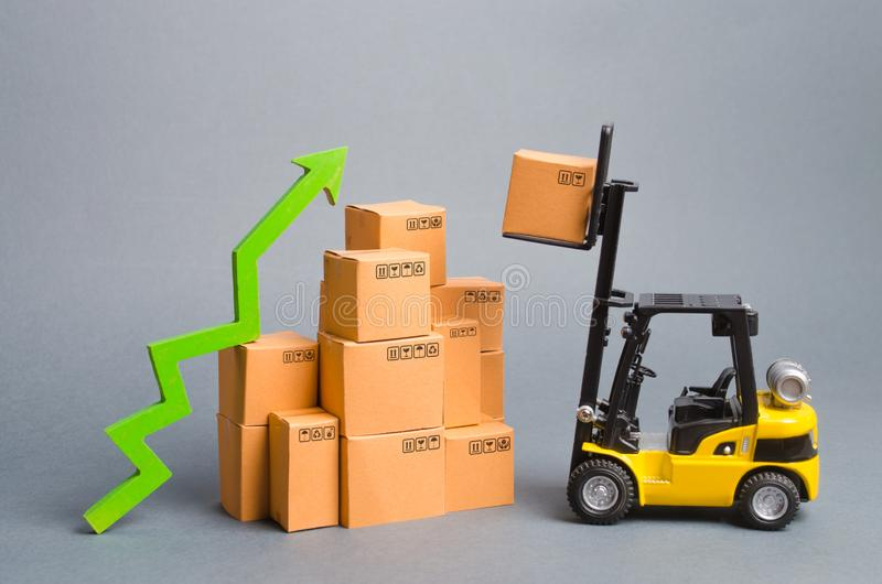 Yellow Forklift truckraises a box over a stack of boxes and a green arrow up. High trade volumes, increased production, storage. Infrastructure. raise economic stock image