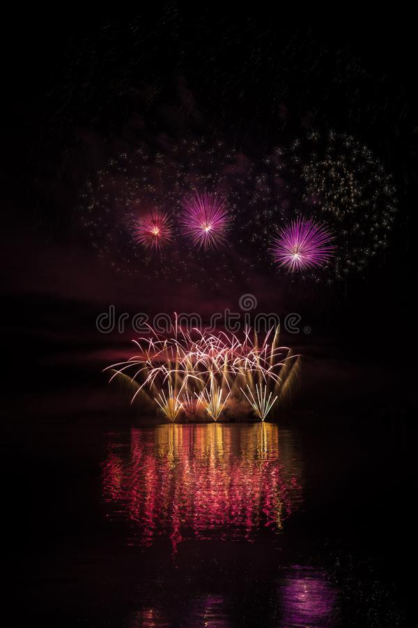 Yellow fountain, violet stars with bright glitter in rich fireworks over Brno`s Dam with lake reflection royalty free stock images