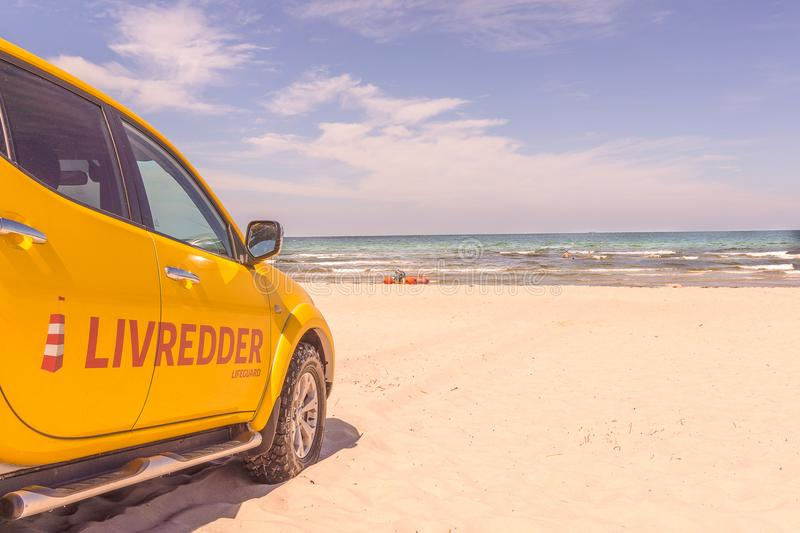 A yellow four-wheel drive car for the lifeguards on a sunny danish beach. Rorvig, Denmark, July 20, 2018 stock image