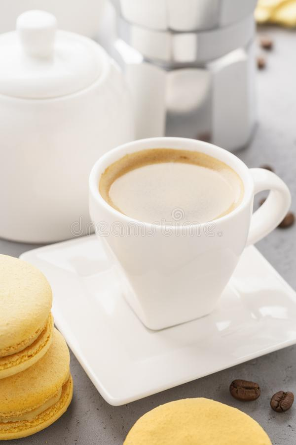 Yellow french macarons with fruit filling and a cup of espresso. Coffee time stock image