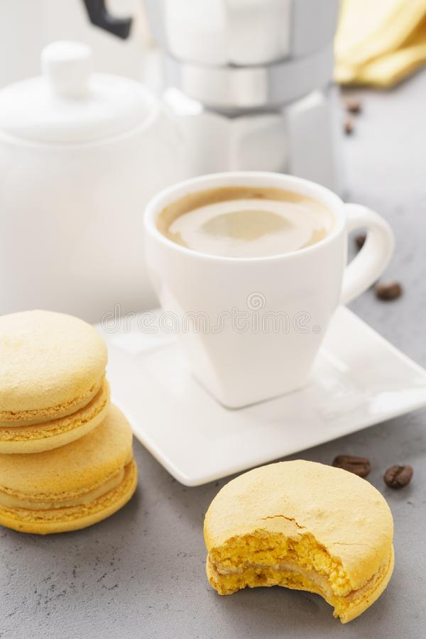 Yellow french macarons with fruit filling and a cup of espresso. Coffee time stock photography