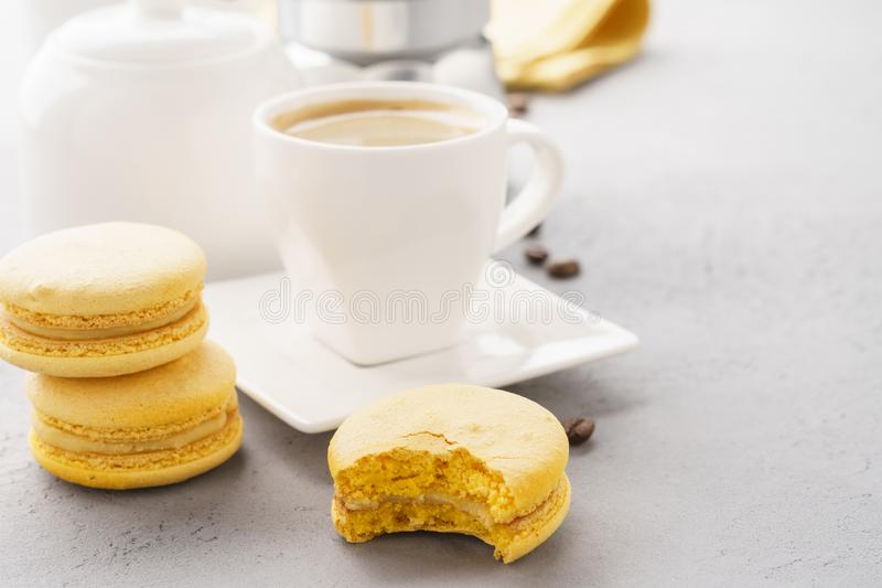Yellow french macarons with fruit filling and a cup of espresso. Coffee time stock images