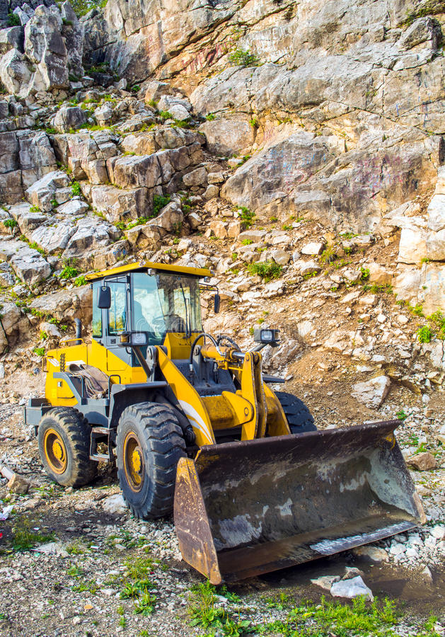 Yellow front end loader machine. Scooping up big stones in a quarry royalty free stock image