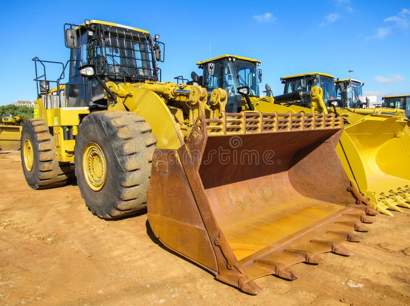 Yellow Front End Loader with rusted load bucket. With blue sky background stock photos
